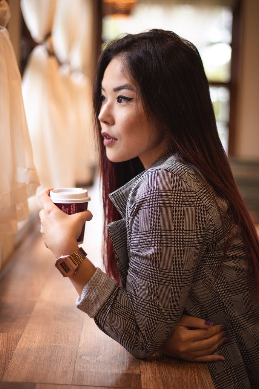 woman leaning on table holdingcup