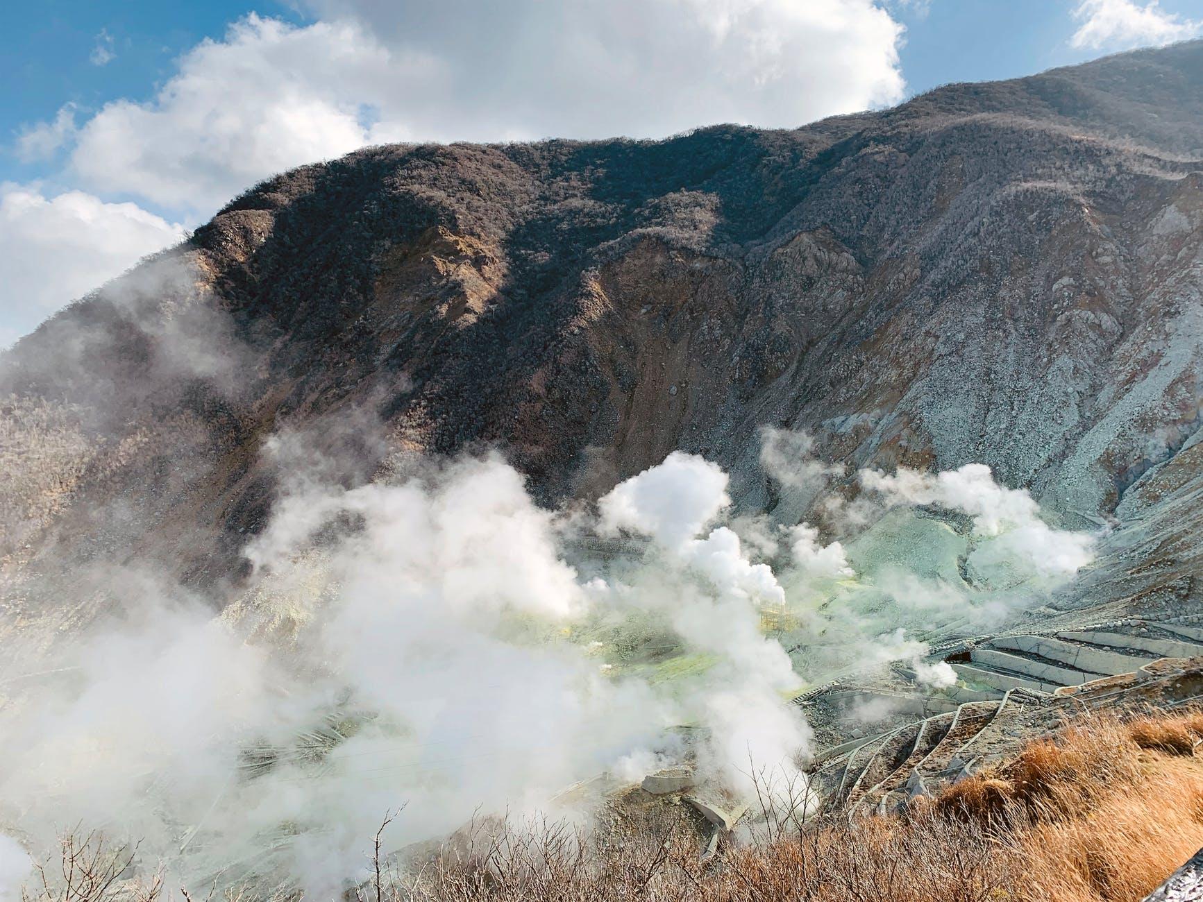 dramatic volcanic terrain with fumingmist