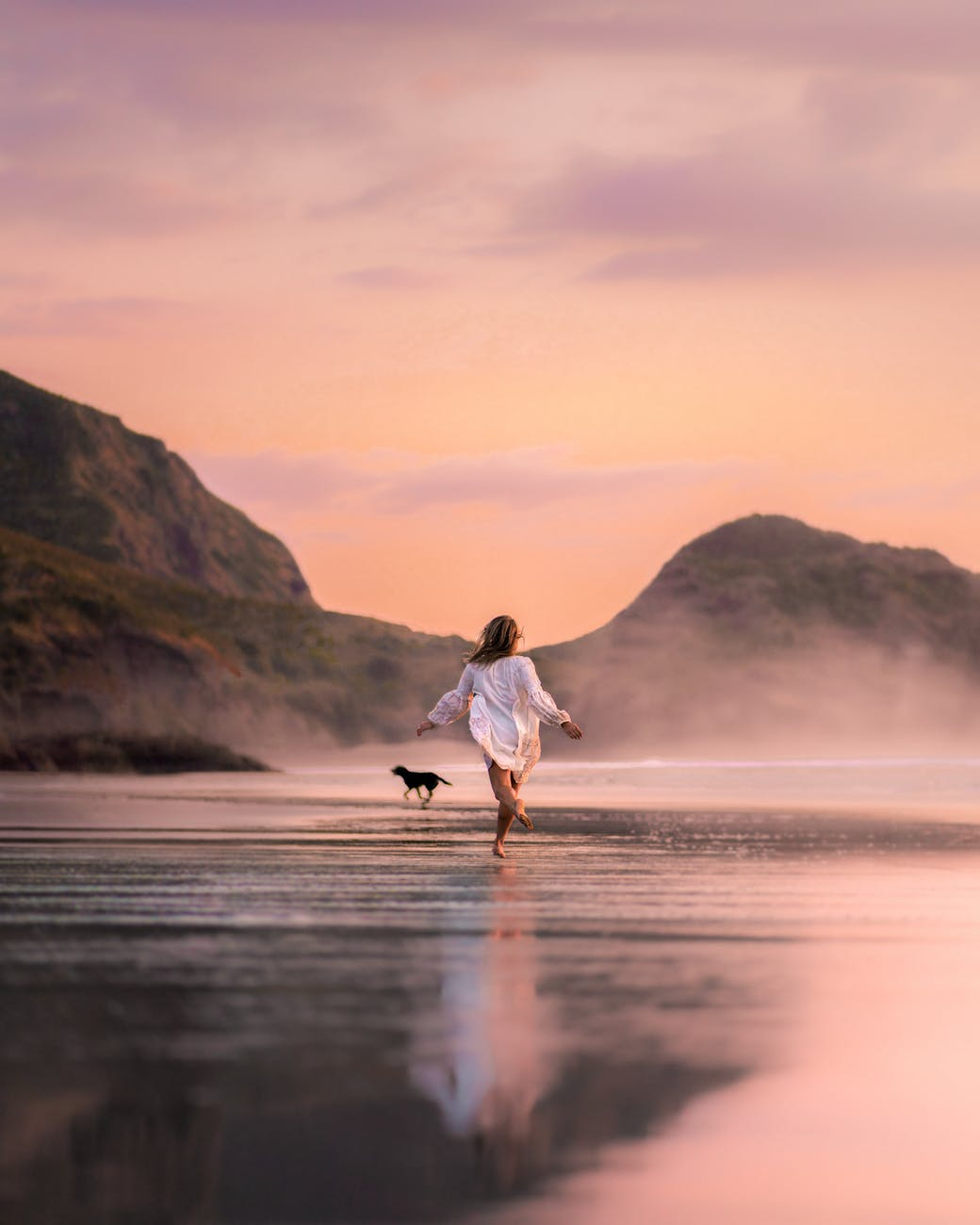 unrecognizable woman with dog running on picturesque beach intwilight