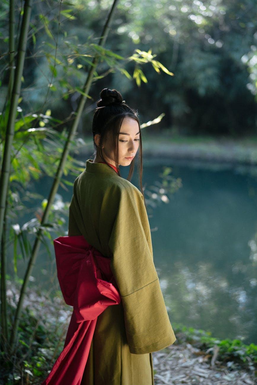 woman in green kimono standing near body ofwater